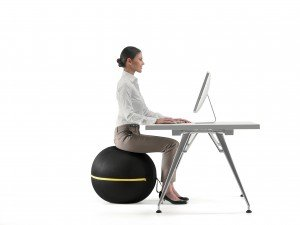 A woman at a desk whilst active sitting on a Wellness Ball