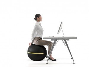 Business woman sitting at desk on Wellness Ball relieving back pain through yoga exercise