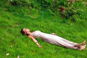 Woman lies down in quiet place for her relaxing yoga stretches
