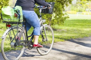 An obese woman riding a bike with a rear rack at the back during a sunny day in the park during spring