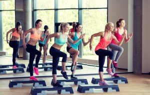 A group of young women during a fitness class working out with steppers on a bright day in the gym