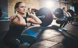 A strong young woman doing heavy duty squats in the gym with a barbell