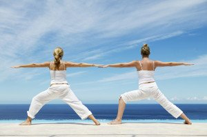 due women doing tai chi yoga and pilates classes on the beach on a sunny day