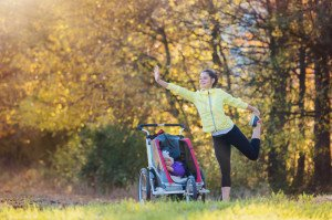 A young mother practising yoga poses in a park on a bright day during autumn with her daughter in a jogging stroller