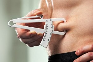 Young Man Measuring Fat Belly With Skinfold measurement