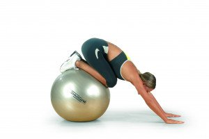 girl bending her knees on a wellness ball by technogym