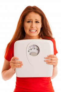 A woman holding a set of bathroom scales
