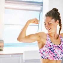 A woman flexes her arm muscle